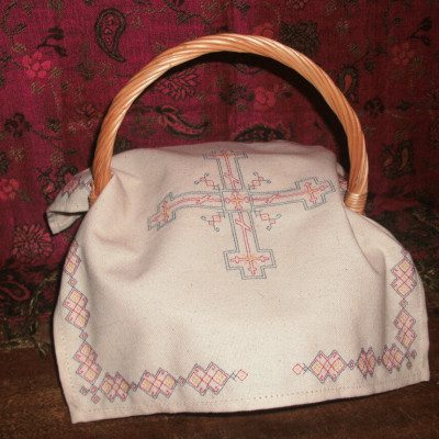 Embroidered Pascha basket cover on a wicker basket.
