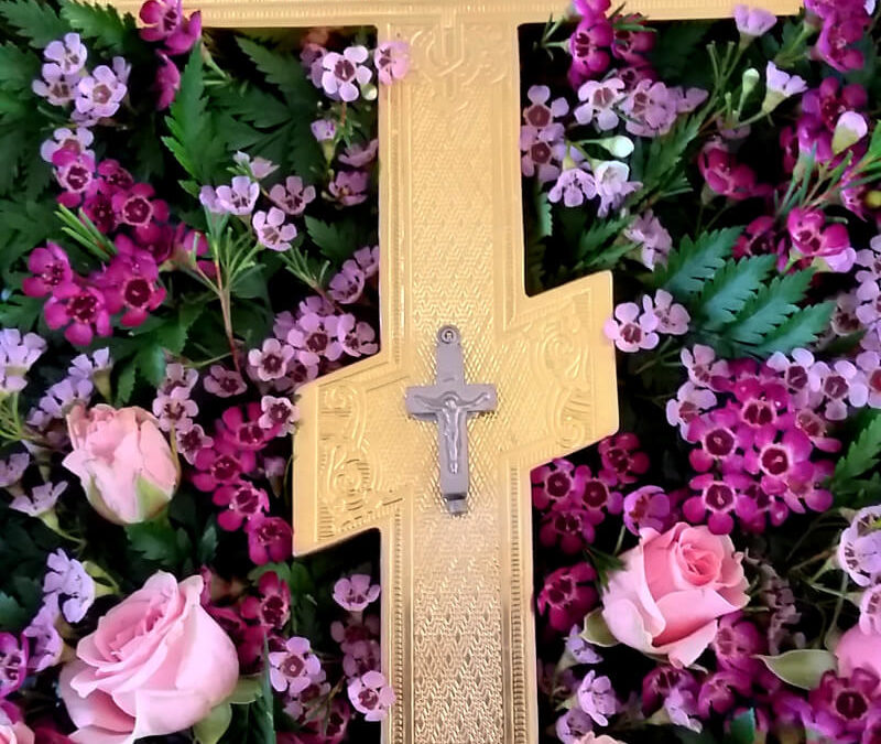 Small cross-shaped silver reliquary affixed to a larger gold cross and displayed on a bed of roses and other flowers
