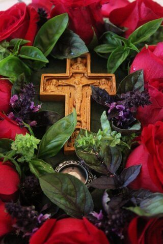 Carved wooden crucifix on a bed of green and purple basil and red roses