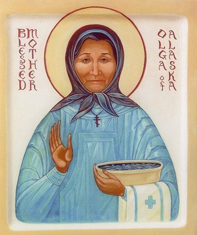In the icon, Matushka Olga is wearing a light blue garment and a dark blue headscarf. She is wearing a small cross on a chain around her neck. She is holding a small bowl of water in her left arm, which is draped with a white towel embroidered with a blue cross.
