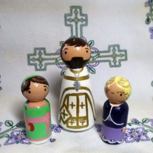 Three peg dolls, a priest in Paschal vestments, along with a smaller Catherine and Elizabeth dolls