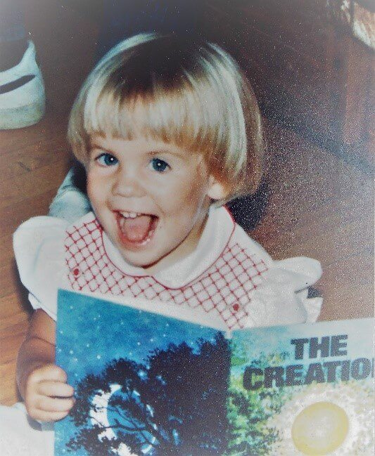 "Nicole Roccas when she was two or three, holding a book titled ""The Creation"""