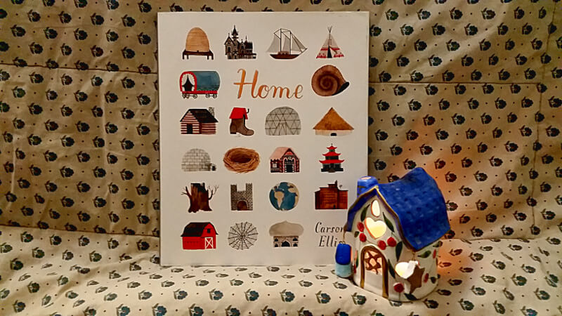 Carson Ellis's debut picture book, Home. In front of the book is a tiny ceramic house with heart-shaped windows and a candle burning inside.