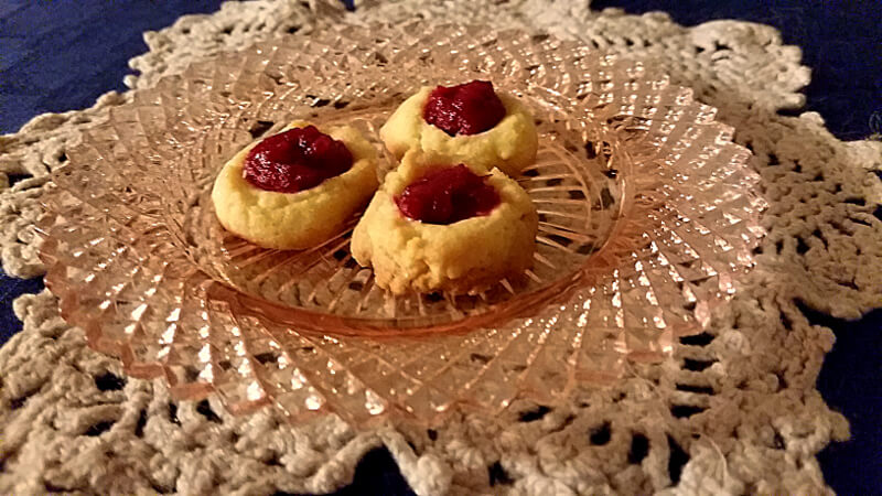 Three thumbprint cookies on a pink glass plate