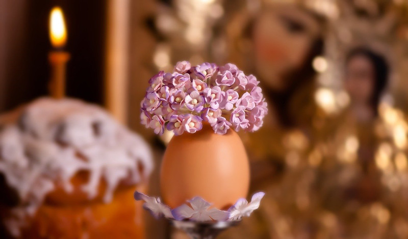 Tiny flowers in an eggshell vase; in the background, an icon of the Theotokos and a loaf of Easter bread with a candle
