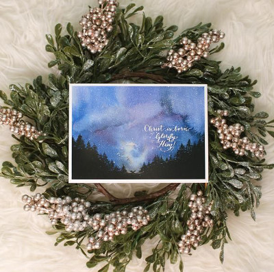 "Card with the words ""Christ is born! Glorify him!"" in calligraphic script over a water color painting of a dark night sky, and pine-covered hills off in the distance."