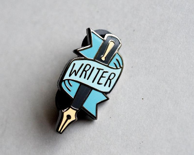 "an enameled pin of a fountain pen with the word ""writer"" on a banner wrapped around it"