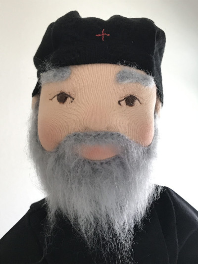 Monk doll with gray beard and bushy gray eyebrows