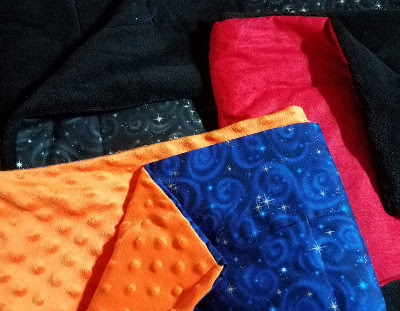 weighted blanket with a blue galaxy print on one side and a nubby orange fabric on the other