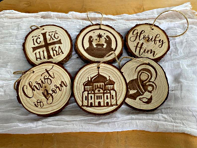 six wooden ornaments: Christ is born, Glorify him, Mary and Jesus, a manger scene, a church with onion domes, and a Christogram cross