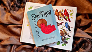 With Two She Flew, a children's book with a stylized red bird on the cover, sitting on a field guide to birds, open to the page with cardinals