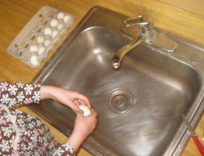 Holding the egg over the kitchen sink when you break it