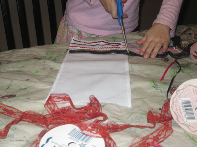 a child cutting lace after gluing it to their basket cover