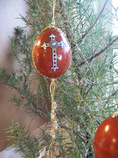 red egg trimmed with ribbon and a cross