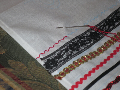 a basket covere trimmed with lace and rickrack; a line of embroidered zig zag pattern is in progress