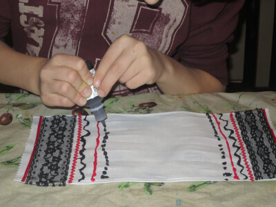 A child using fabric paint to add a row of dots to their basket cover
