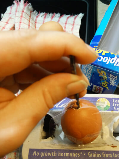 using a drill bit to enlarge the hole in an egg to make it easier to blow